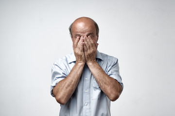 Mature caucasian man in blue shirt covering his face with hands over gray background. Toned studio shoot