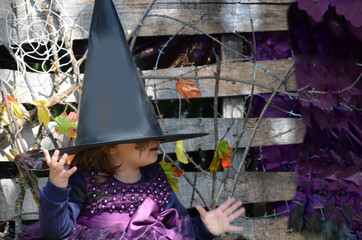 Little witch,A girl in a witch costume,Girl dressed as a witch in the forest with hat, halloween.