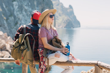 Couple Travelers Man and Woman sitting relax in a hike. Hikers with backpacks in the mountains by the sea. Love and Travel happy emotions Lifestyle concept. Young family traveling active adventure.