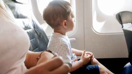 Adorable toddler boy sitting in airplane and looking out of the window at sunny day