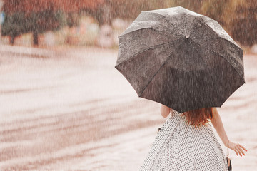 Wet weather. Autumn rain. Depressed girl in polka dots dress hold  black umbrella. Raining in city. Wet umbrella against the backdrop of the street. Woman was caught in the rain. Alone depressed girl