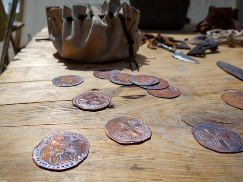 Ancient coins and purse on wooden table
