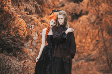 Goth couple in halloween costume. Gloomy vampire in baroque clothes. Redhead woman vampire in black baroque dress. Goth clothes for halloween party. Gloomy couple on autumn background.