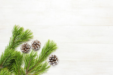 Christmas background, green pine branches, cones decorated with snow on white wooden table. Creative composition with border and copy space design top view. New Year's, holiday, christmas, decoration