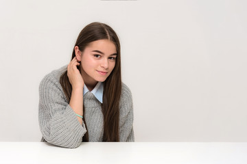 Portrait of a beautiful teenage girl on a white background with different emotions sitting at a table.