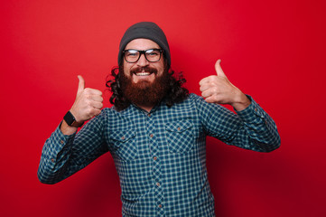 Portrait of happy man with beard showing thumbs up over red background