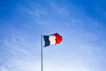 French flag waving the wind in Paris. Clear blue sky background. France.