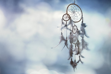 Dream catcher on blue background with copy space