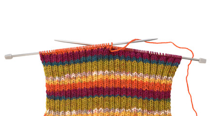 Knitting pattern on needles of woolen threads colorful isolated on white.