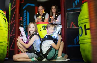 Kids sitting back to back with laser guns