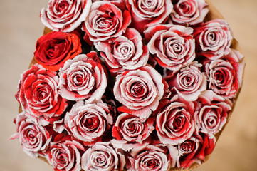 Adorable red roses decorated with white glitter sand