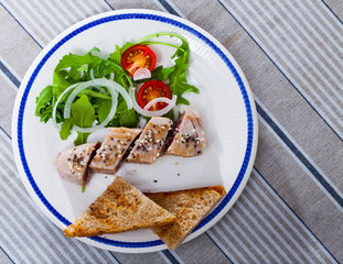 Tasty lightly fried tuna, served at plate with bread and greens