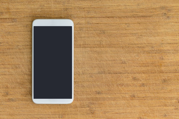 Isolated smart phone on scratched wooden table