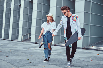Happy young couple hold hands and walking together with skateboards on modern street in windy weather.