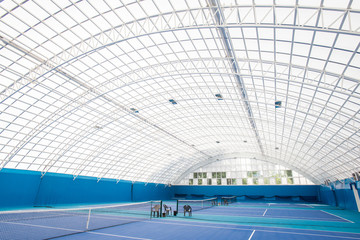 Background shot of modern indoor tennis court interior with glass dome, copy space