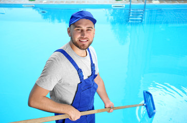 Male worker cleaning outdoor pool with scoop net