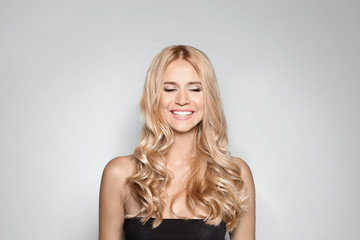Beautiful woman with healthy long blonde hair on light background