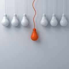 Think different concept One hanging orange light bulb standing out from the dim unlit white light bulbs on white wall background leadership and individuality creative idea concepts 3D rendering