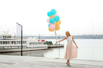 Beautiful young woman with bunch of balloons outdoors. Space for text