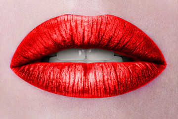 Close up view of beautiful woman lips with red matt lipstick. Open mouth with white teeth. Cosmetology, drugstore or fashion makeup concept. Beauty studio shot. Passionate kiss