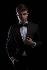 portrait of confident young man in black tuxedo holding collar