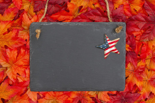 Autumn time in the USA with a chalkboard with a retro stars and strips star and fall leaves