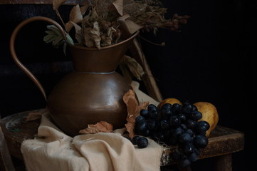 Still life with dry bouquet in a copper jug and fruits.