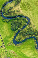 Foto op Plexiglas Rivier Aerial view on winding river in green field
