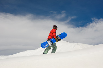 Young male snowboarder walking up the hill with the snowboard