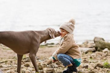 Happy little girl play with a dog on the autumn beach