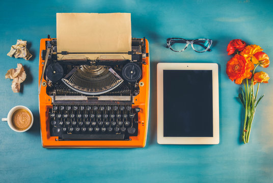 Workspace with orange vintage typewriter on blue background, toned