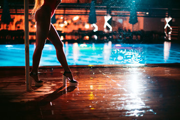 PJ or go-go dance in the rain on a wooden dance floor under an umbrella near the pool. Abstract blurred image