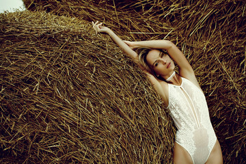 fashion outdoor photo of gorgeous sexy woman in elegant lingerie posing outdoor against a stack of hay in a summer day