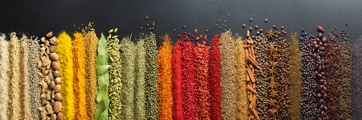 Foto op Plexiglas Kruiden Colorful collection spices and herbs on background black table. Mediterranean condiments for decorating packing with food.