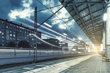 Highspeed train departs from the station platform at evening time.