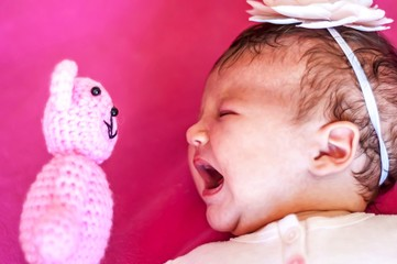 Funny picture of a Caucasian newborn infant baby girl looking at the teddy bear face to face and crying. Discover the new world concept, learning new things. One month old child scared.