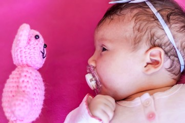 Funny picture of a Caucasian newborn infant baby girl looking at the teddy bear face to face. Discover the new world concept, learning new things. One month old child.