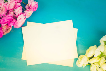 Pink and white ranunculus flowers on blue wooden background with copy space on blank paper notes, retro toned