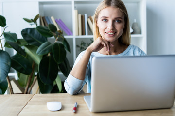 New solution every day. Confident young woman in smart casual wear working on laptop while sitting at her working place in office.