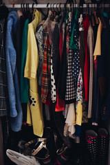 View of different colorful clothing in wardrobe in fashionable store. Stylish shoes and clothes inside modern show room. New collection and sasone sale. Shopping, fashion concept.