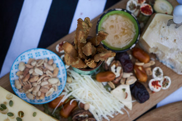 Snacks for beer with different food, top view. Salty and cheese bar of several kinds of cheese, grapes, olives, nuts, fruits  decorated on table. Holiday party outdoors, picnic