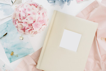 Home office desk with family wedding photo album, pastel colorful hydrangea flower bouquet, peachy blanket, decoration on white background. Flat lay, top view.