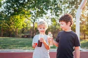 Little boys drinking from bottles