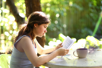 teenager student girl reading book with tea cup