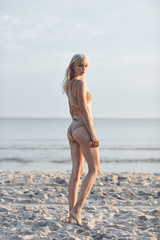 Attractive, slim blonde walking on an empty beach