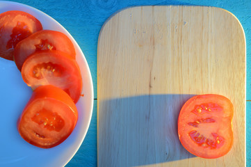tomato slices are laid out on a wooden cutting board and white ceramic plate with a blue-turquoise...