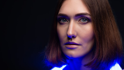 Art portrait of a girl on a black background with blue neon lights. Beautiful eyes, natural beauty, clean skin, facial and hair care. With space under the inscription