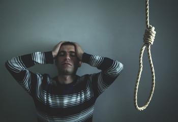 Caucasian depressed man with a noose. Suicide concept