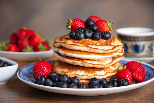 Stack of pancakes with blueberries and strawberries on a blue and white plate with bowls of strawberries and blueberries and a cup of coffee in the background.