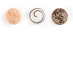 Three sweet doughnuts with chocolate, nuts, white chocolate and coconuts isolated on white background. Top view and copy space